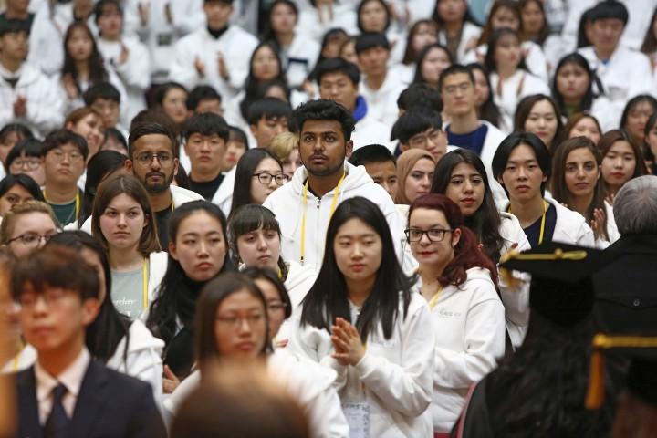 (사진4)외국인 신입생들이 퇴장하는 교수들에게 박수를 치고 있다